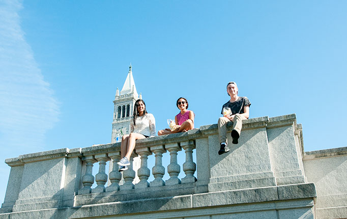 Three students sitting on railing near campanile