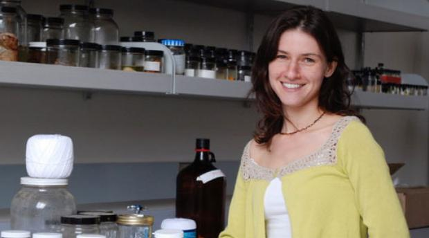 Portrait of Bree Rosenblum standing in a lab in front of glass jars