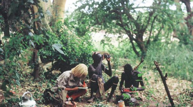 Carr documenting plant collections in the Omo Riverine forest in Ethiopia, with curious Dasanech men attending
