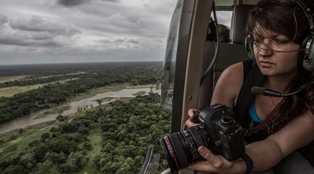 Jen Guyton taking photographs from a helicopter