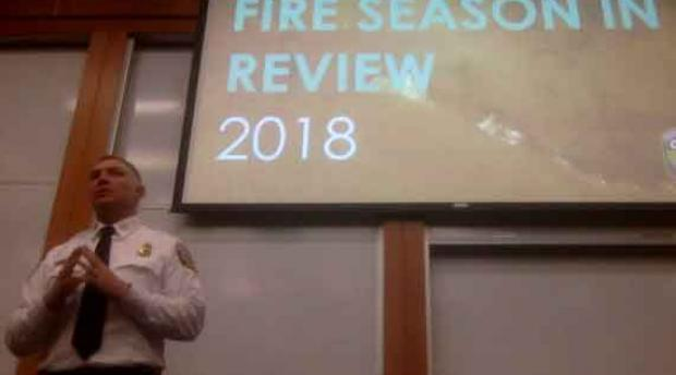 "A man stands in front of a presenting screen that reads ""fire season in review 2018"""