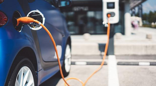 Electric car plugged into charging station