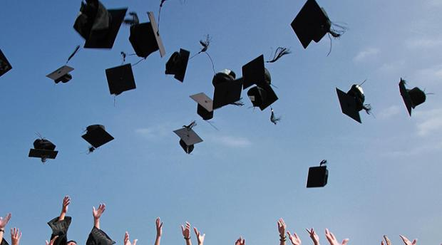 Stock image of group of graduates tossing graduation caps into air