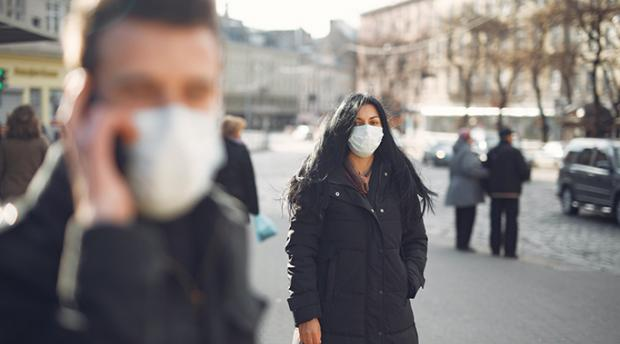Woman and man on street wearing protective face masks